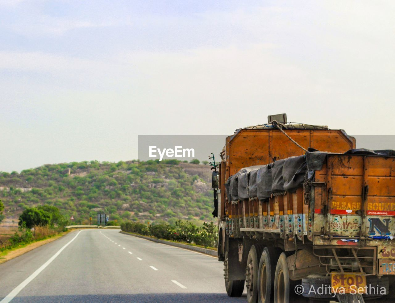 transportation, road, sky, mode of transportation, nature, day, land vehicle, motor vehicle, no people, tree, plant, car, truck, sign, outdoors, symbol, semi-truck, the way forward, travel, road marking