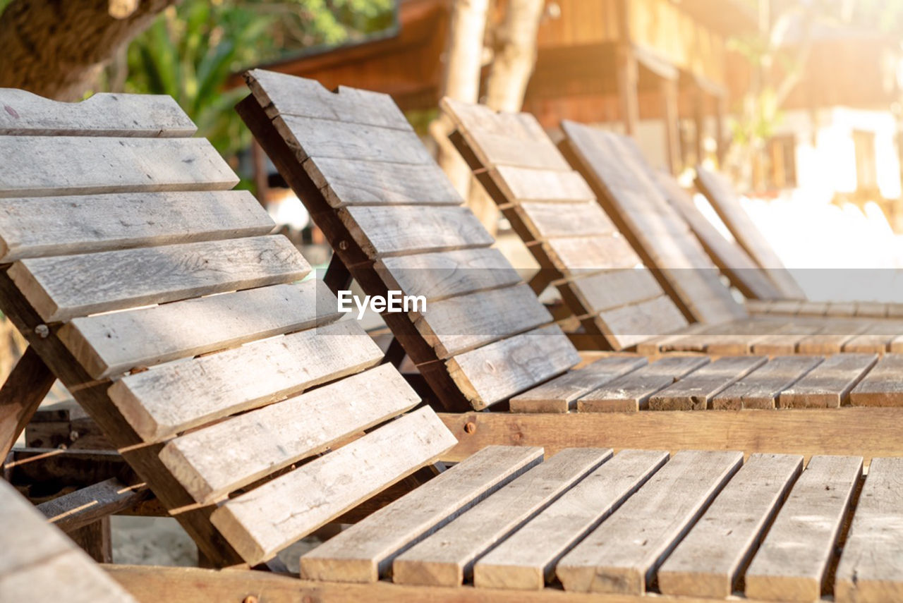 wood - material, day, focus on foreground, no people, close-up, musical instrument, seat, high angle view, piano, music, outdoors, nature, sunlight, selective focus, bench, large group of objects, musical equipment, in a row, stack, piano key, sustainable resources