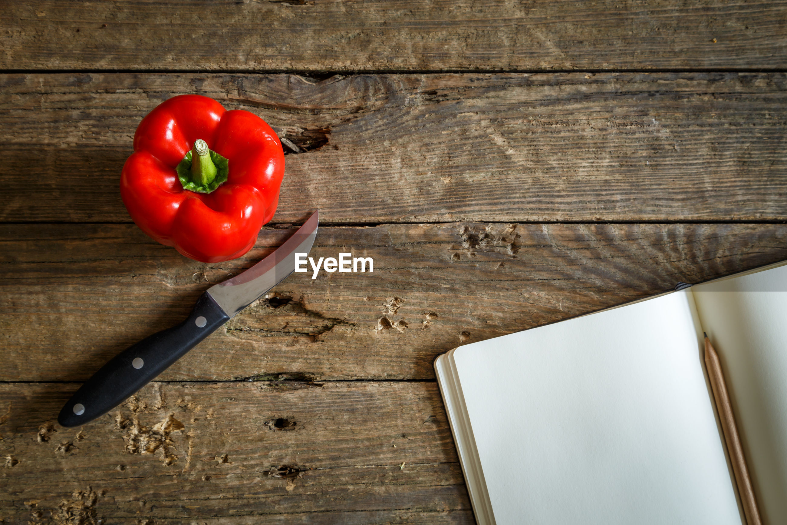 Directly above shot of red bell pepper with knife and diary on wooden table