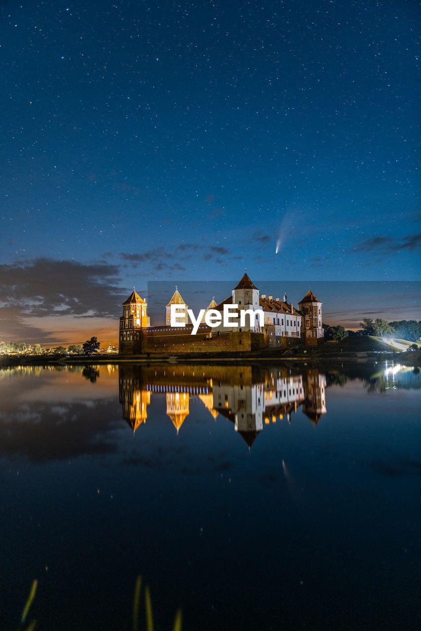 Comet neowise in a night landscape. mir castle in belarus. astronomy.