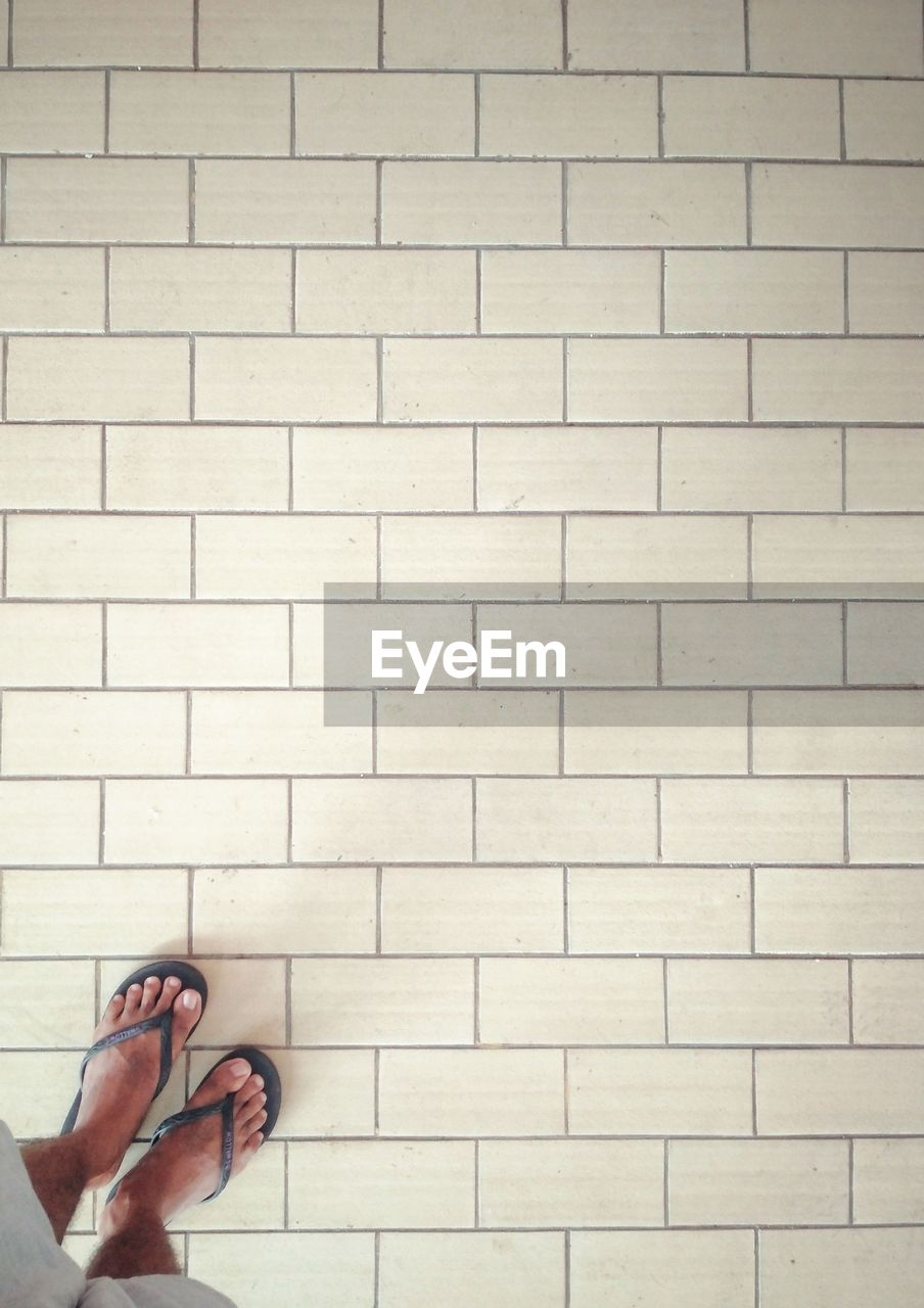 human body part, body part, one person, real people, wall - building feature, human leg, low section, wall, personal perspective, lifestyles, leisure activity, standing, day, hand, unrecognizable person, human hand, shoe, architecture, built structure, human limb, flooring, human foot, brick, finger