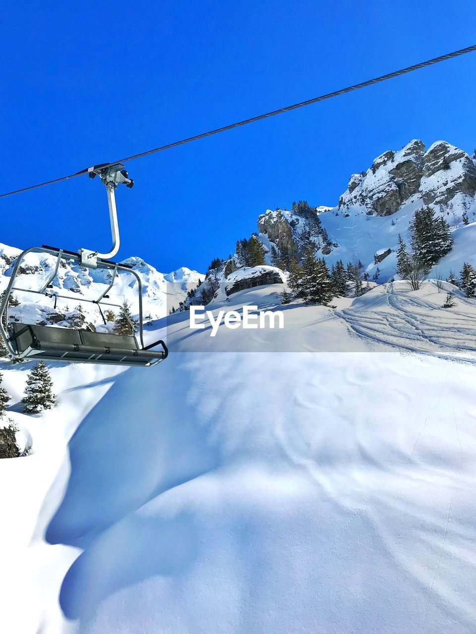 snow, cold temperature, winter, mountain, snowcapped mountain, scenics - nature, sky, nature, beauty in nature, white color, cable car, day, blue, frozen, cable, transportation, covering, mode of transportation, overhead cable car, no people, mountain range, outdoors