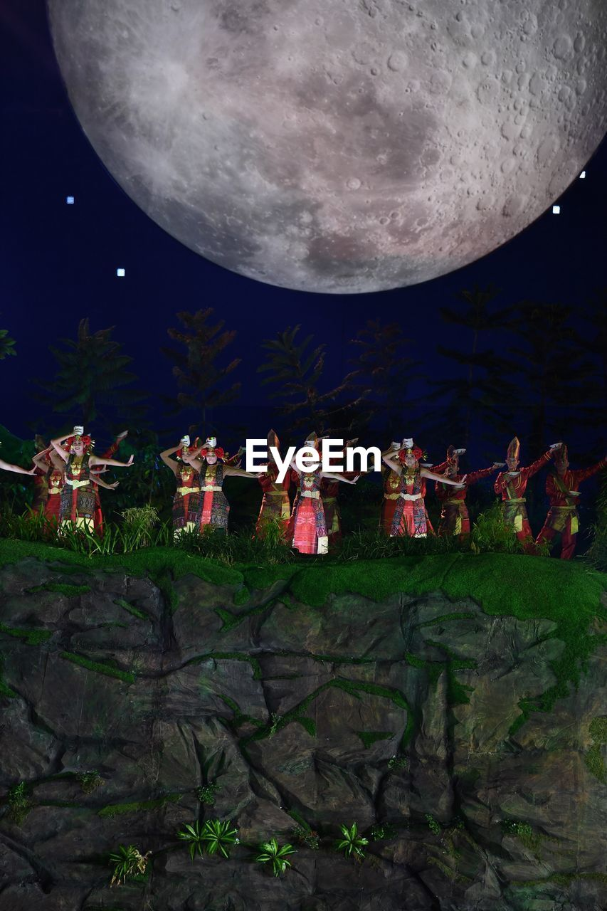 night, arts culture and entertainment, moon, group of people, sky, performance, crowd, real people, music, nature, people, togetherness, musical instrument, women, traditional clothing, leisure activity, performing arts event, outdoors, astronomy, full moon, festival, stage