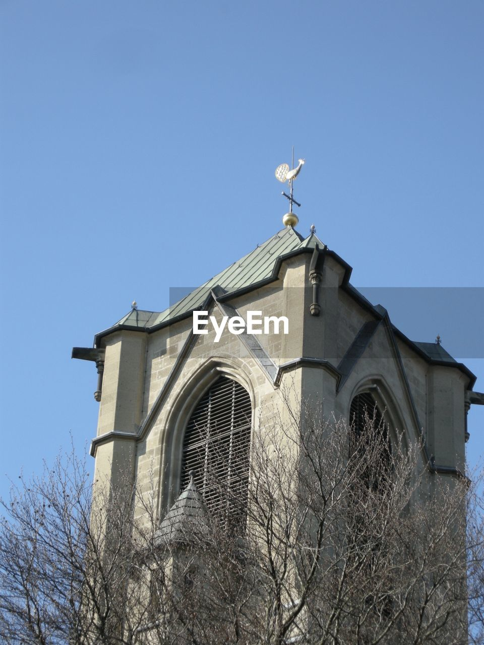 architecture, built structure, low angle view, building exterior, clear sky, spirituality, religion, day, outdoors, place of worship, no people, cross, bare tree, weather vane, history, tree, sky, bell tower, nature