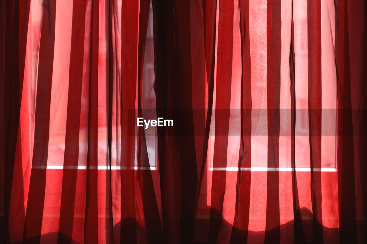 curtain, red, textile, indoors, no people, window, full frame, pattern, home interior, backgrounds, hanging, close-up, sunlight, day, nature, shadow, pink color, stage theater, arts culture and entertainment, stage, nightlife