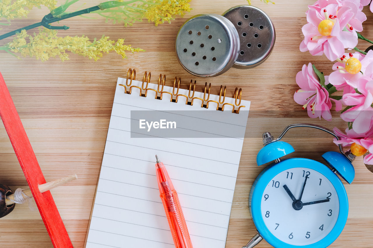 table, plant, flower, flowering plant, indoors, still life, directly above, publication, wood - material, book, high angle view, pencil, pen, spiral notebook, no people, time, writing instrument, paper, clock, nature, note pad