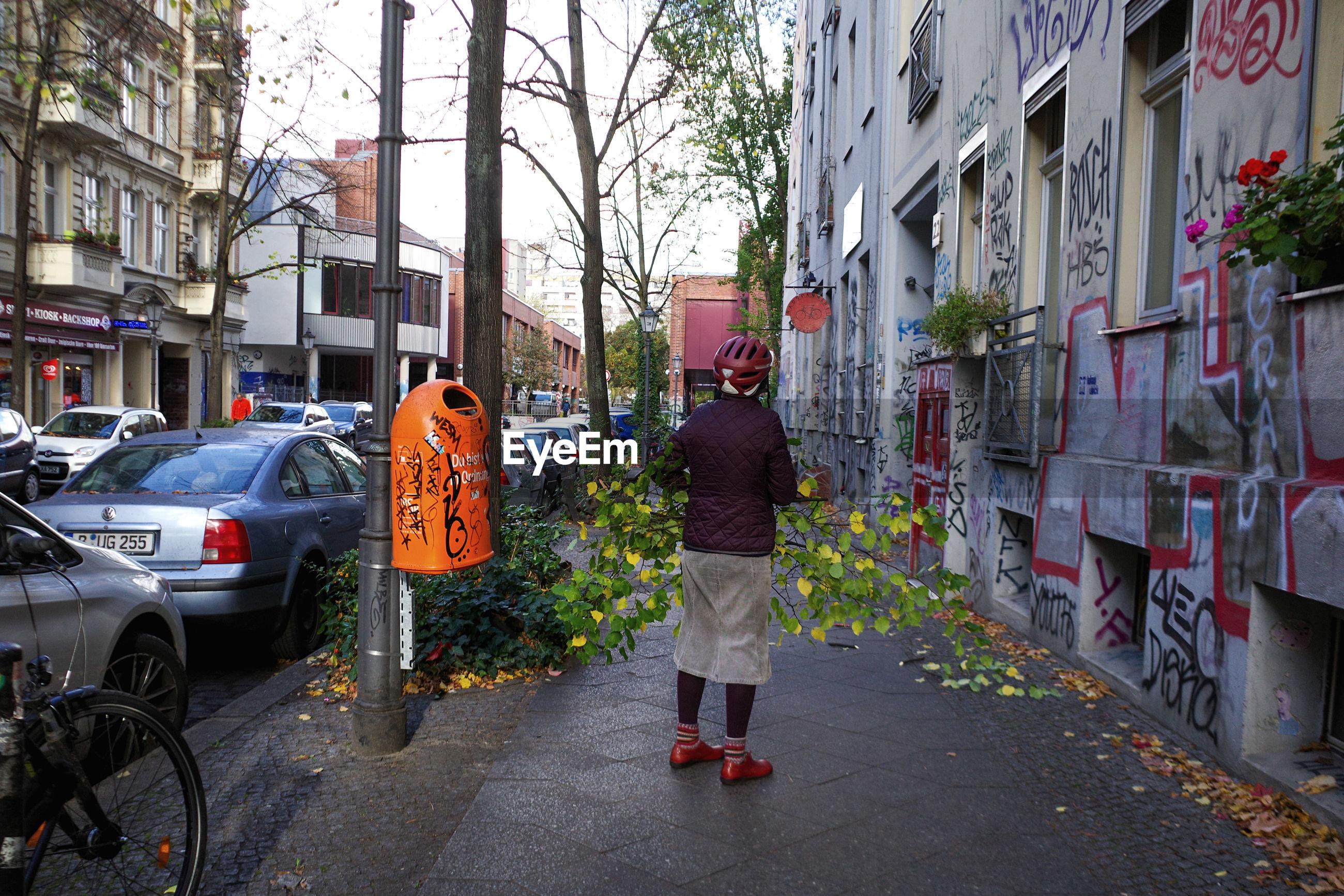 REAR VIEW OF MAN WALKING ON STREET AMIDST CITY