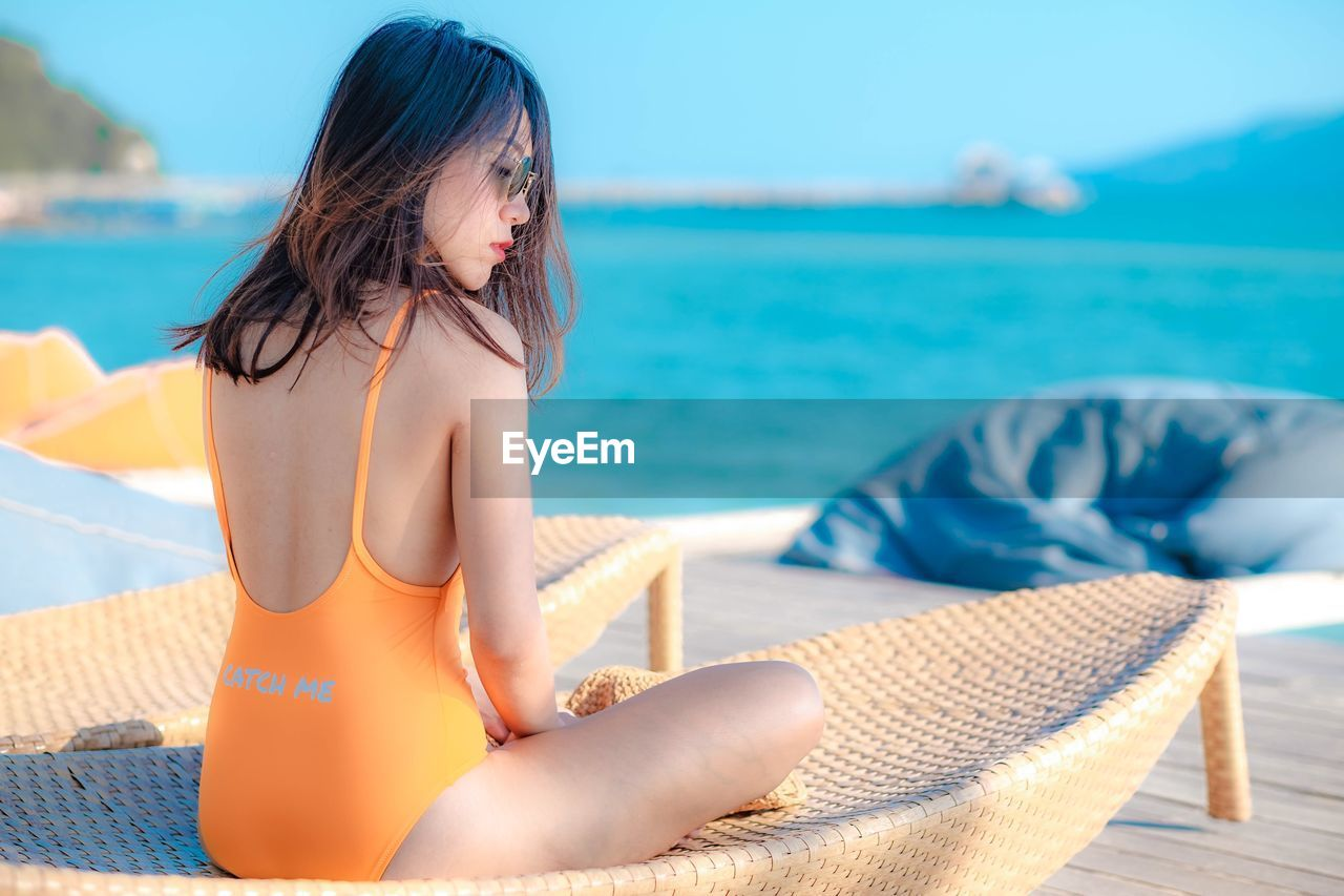 Beautiful woman sitting on seat against sea