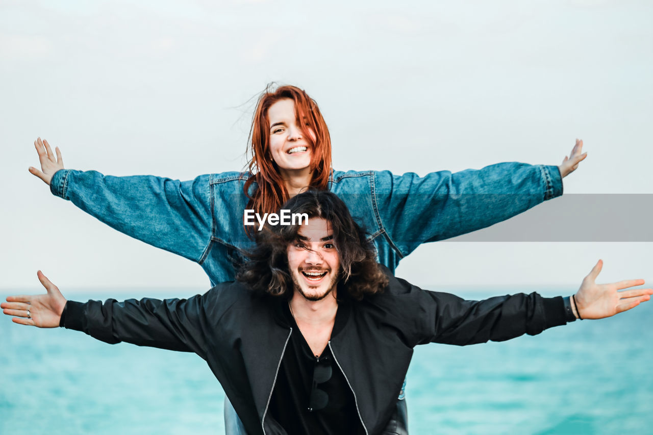 happiness, smiling, emotion, human arm, two people, young women, portrait, togetherness, young adult, real people, front view, positive emotion, limb, looking at camera, leisure activity, women, bonding, fun, arms raised, arms outstretched, couple - relationship