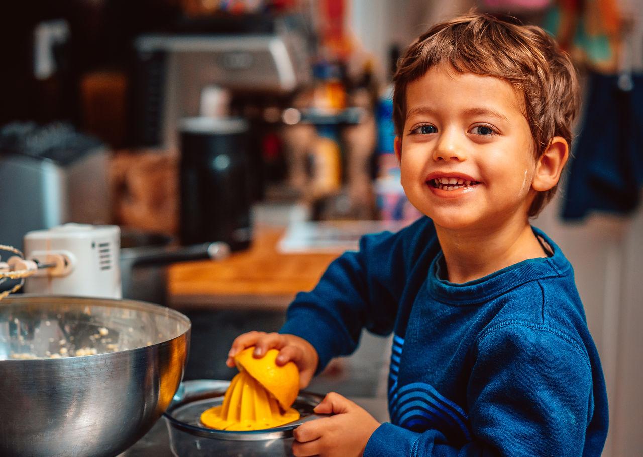 Portrait of smiling boy making lemon juice at home