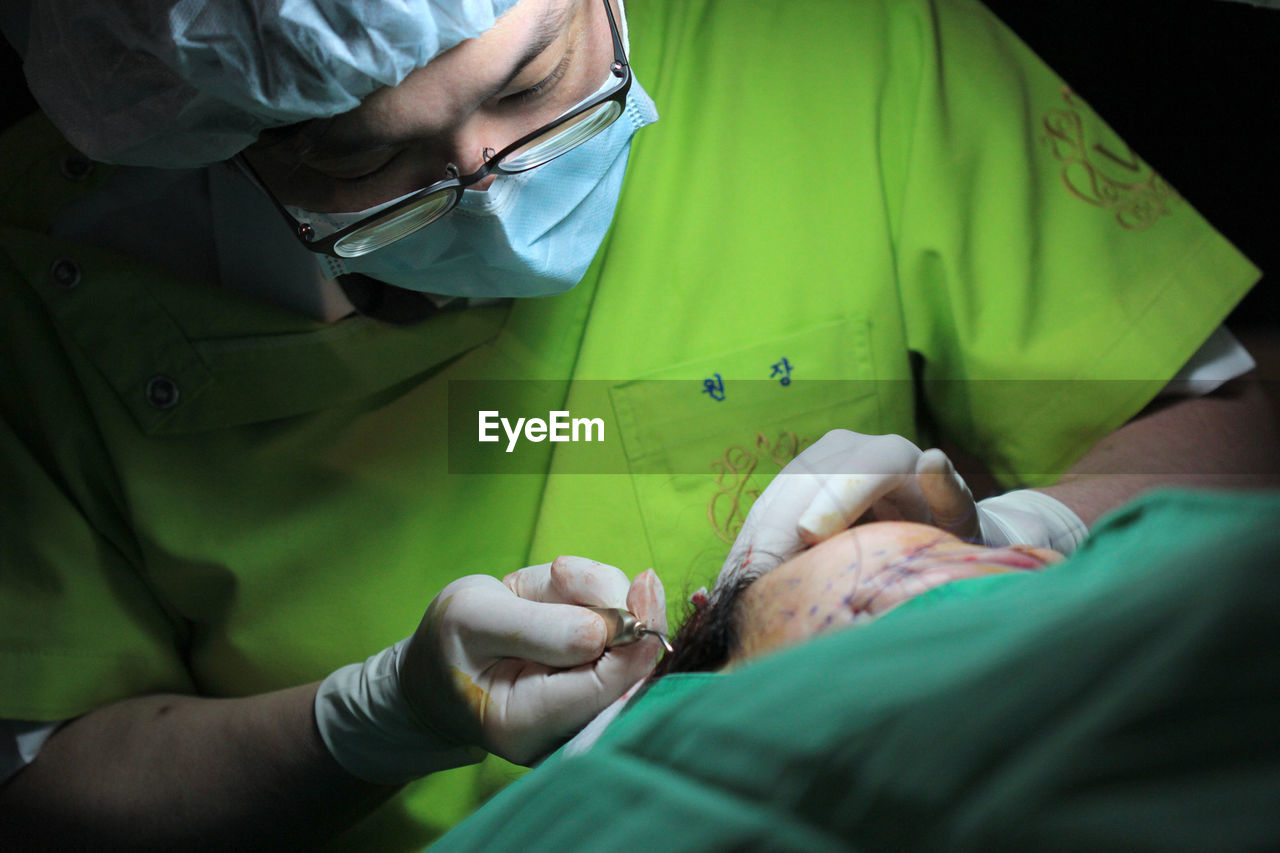 Doctor Performing Surgery On Patient At Operating Room