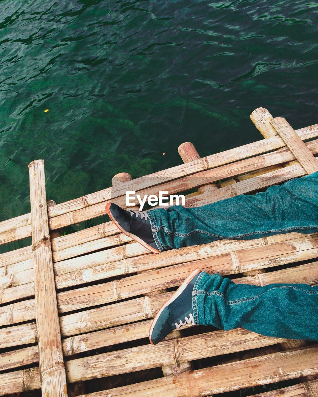 Low section of man relaxing on wooden raft
