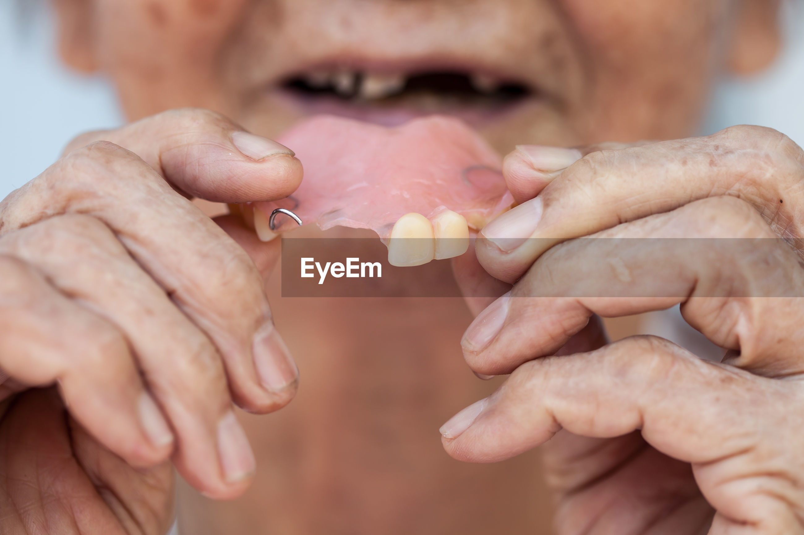 Cropped image of senior woman holding dentures
