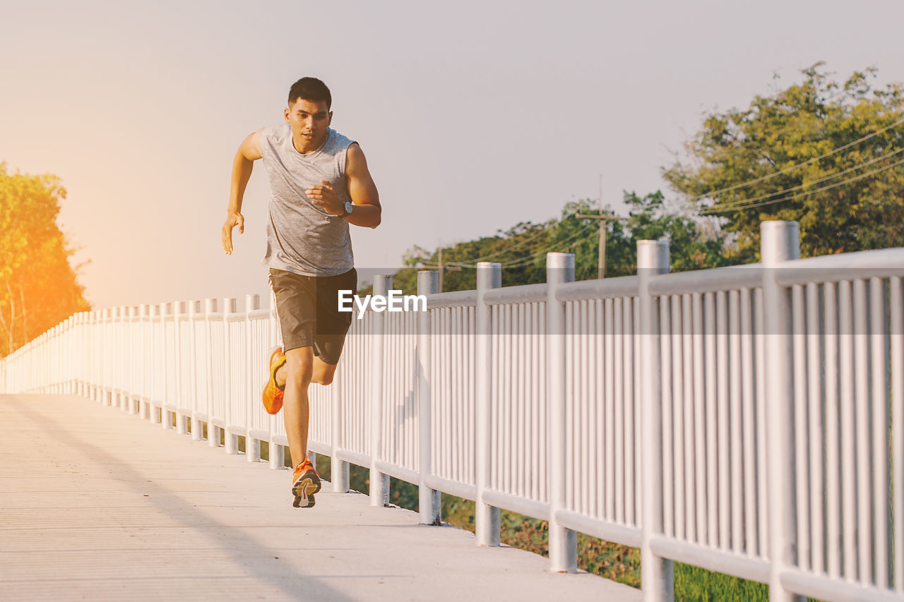 real people, lifestyles, full length, one person, young adult, leisure activity, front view, railing, day, footpath, exercising, young women, built structure, casual clothing, bridge, adult, motion, architecture, shorts, effort