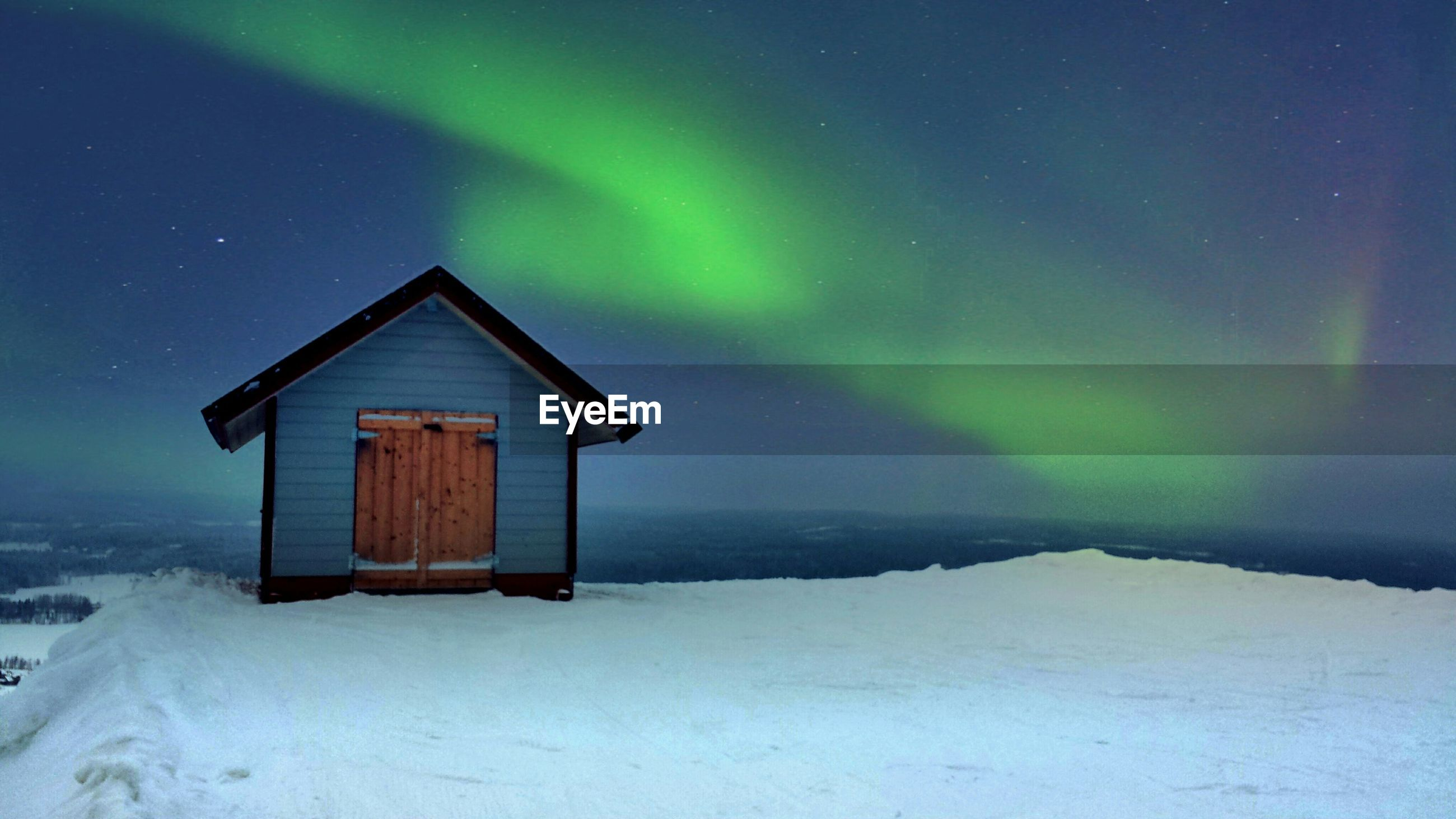 House on snow landscape against northern lights