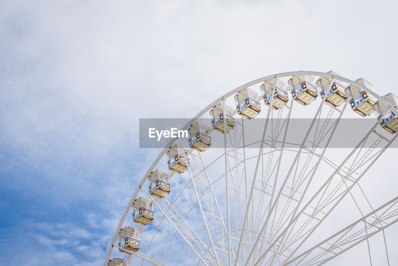 Low Angle View Of Ferris Wheel Against Cloudy Sky