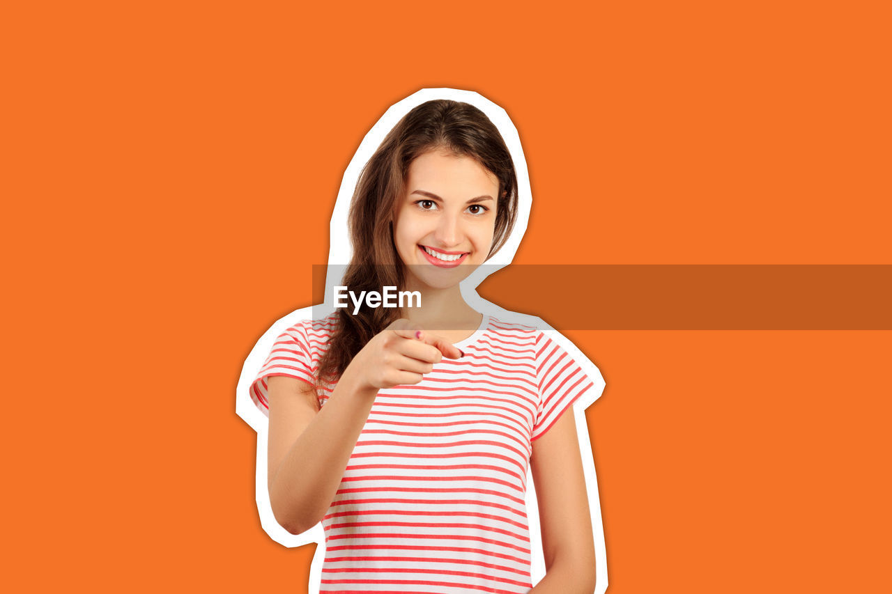 Portrait of beautiful young woman pointing cut out against orange background