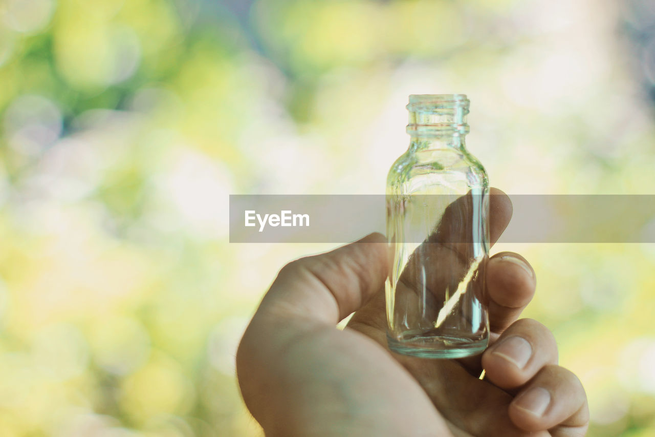 Nature Body Part Bottle Close-up Container Day Finger Focus On Foreground Glass Glass - Material Hand Holding Human Body Part Human Hand Human Limb Lifestyles Mock Up Mockup Nature One Person Outdoors Real People Sunlight Transparent Unrecognizable Person