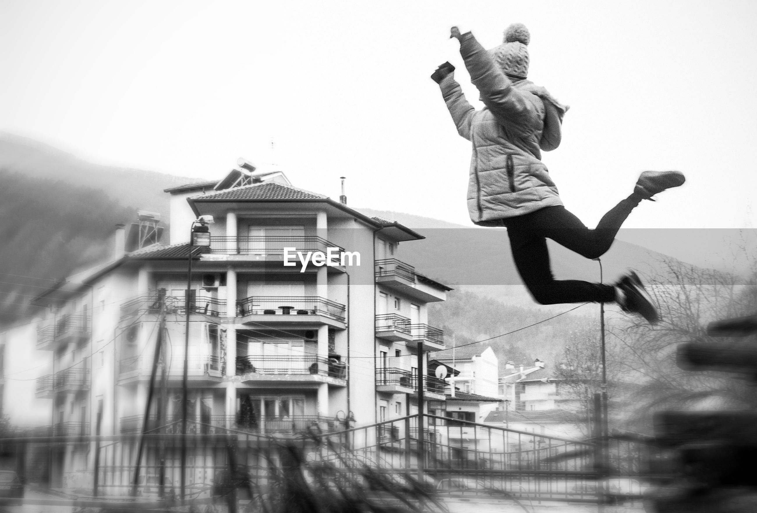 Woman jumping against buildings in city