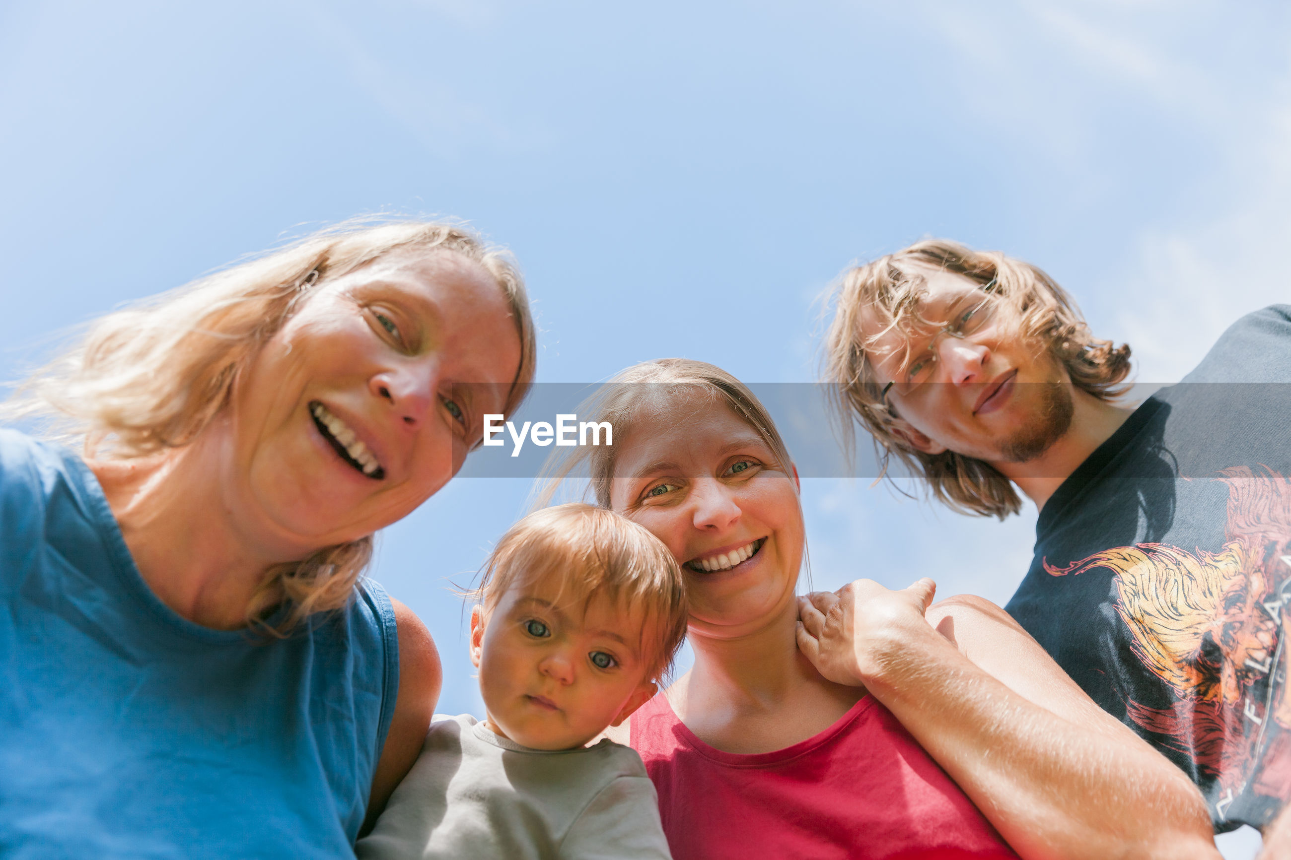 Low angle portrait of family against sky