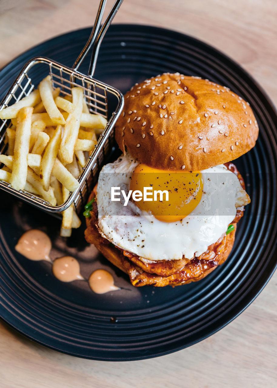 High Angle View Of Egg Burger Served On Table