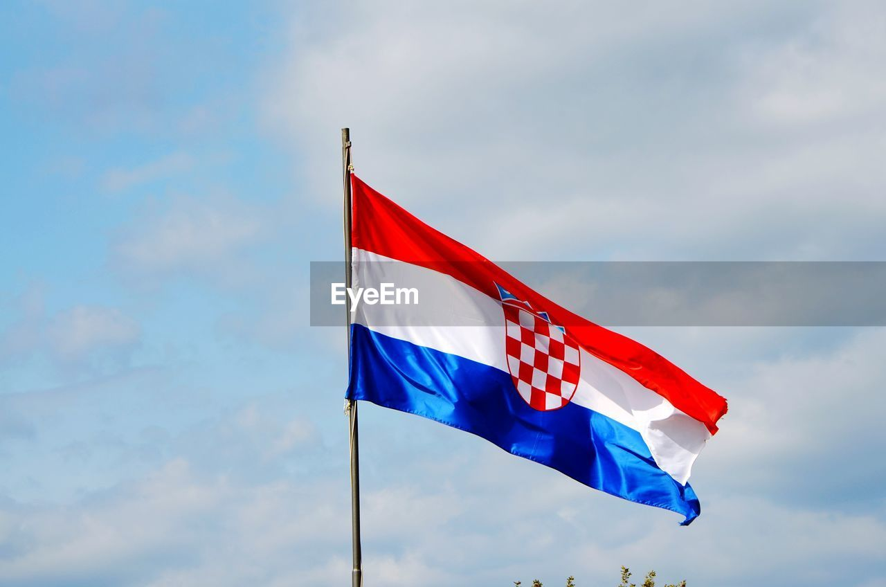 Low angle view of croatian flag waving against sky