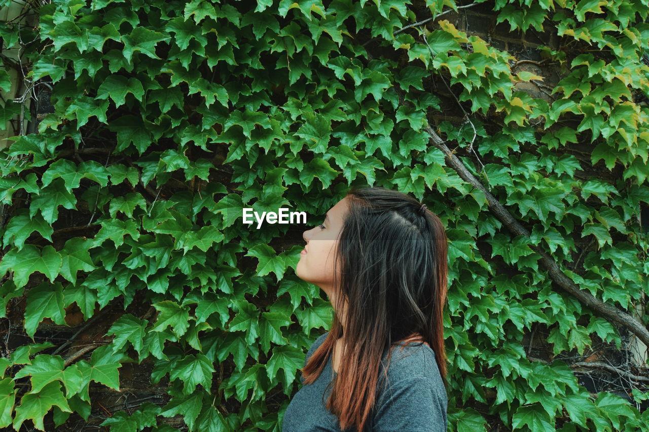 Teenage Girl By Creeper Plants