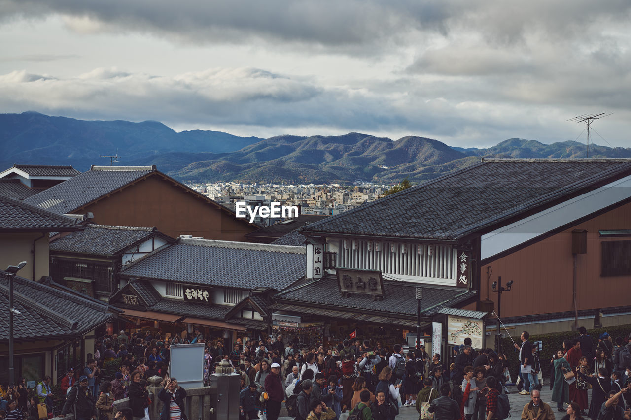 architecture, building exterior, built structure, mountain, crowd, large group of people, cloud - sky, sky, group of people, city, real people, building, mountain range, women, nature, day, adult, outdoors, crowded, spectator, townscape