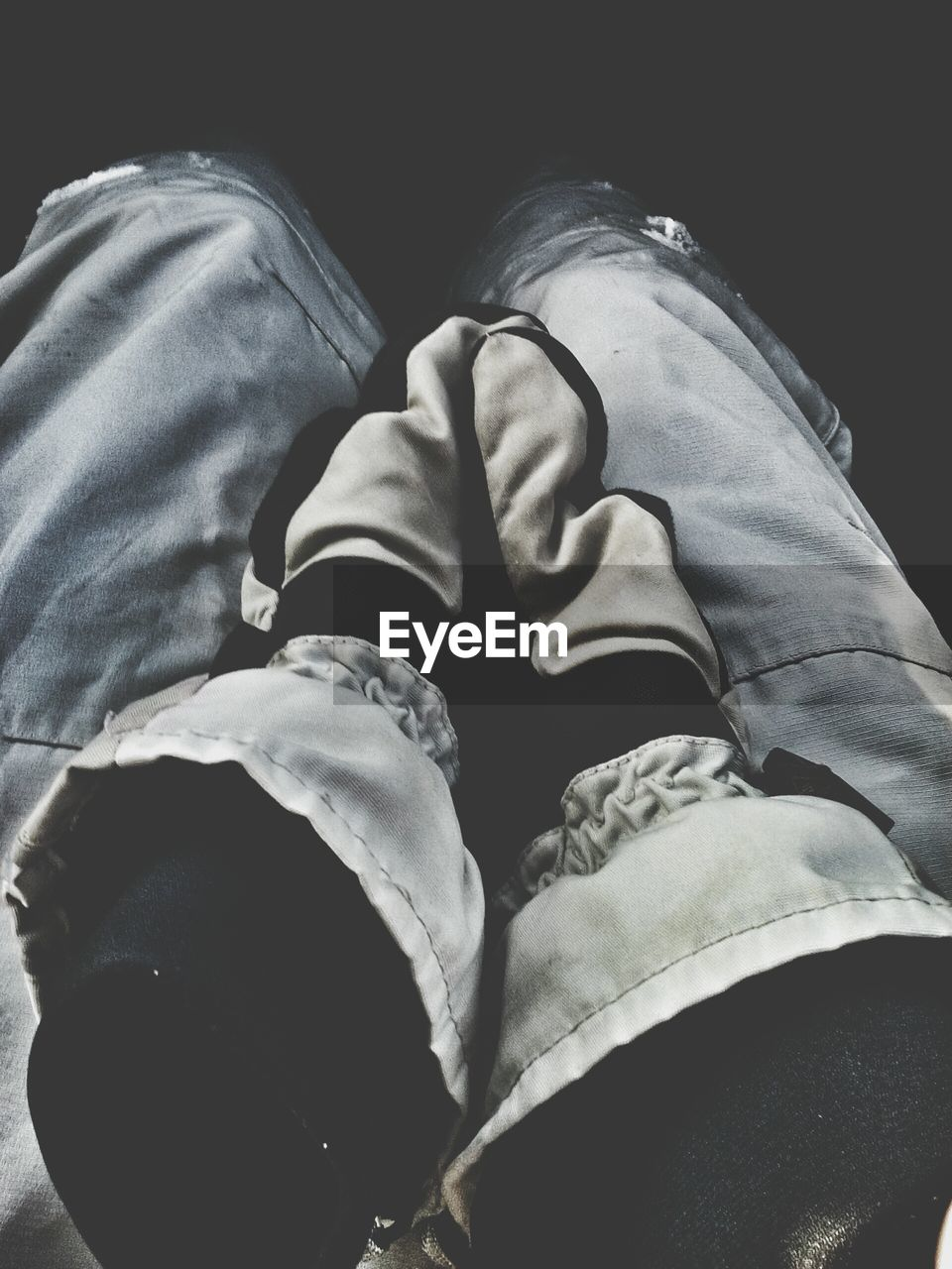 low section, human leg, one person, real people, casual clothing, jeans, shoe, human foot, human body part, lifestyles, leisure activity, men, relaxation, close-up, day, sitting, indoors, adult, people