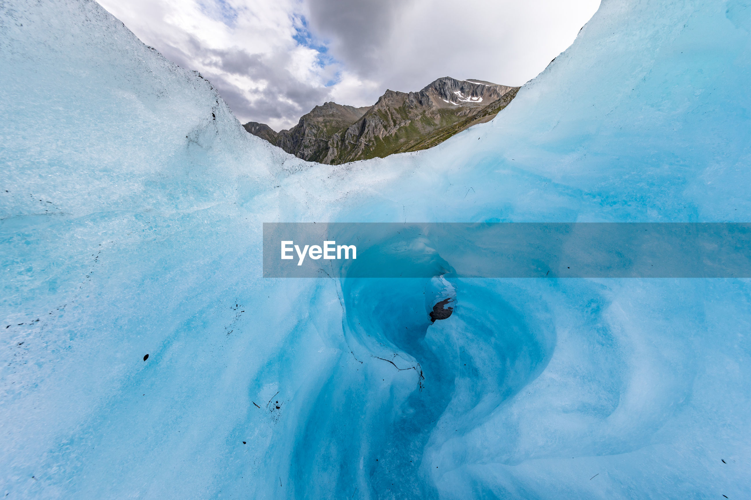 Low angle view of ice formation against cloudy sky