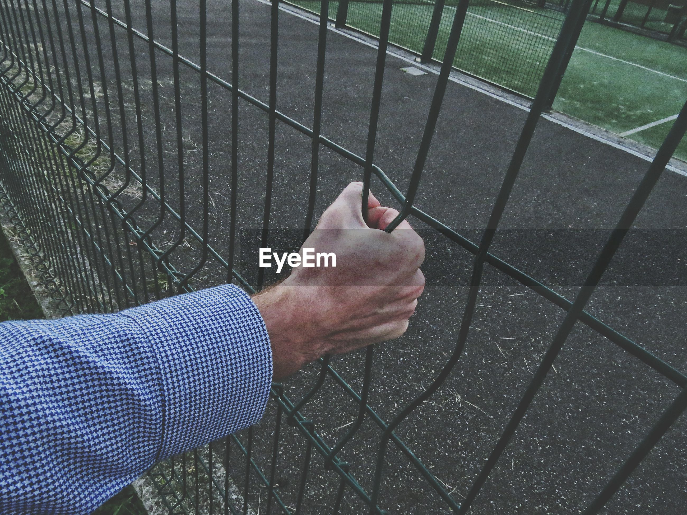Cropped hand holding fence