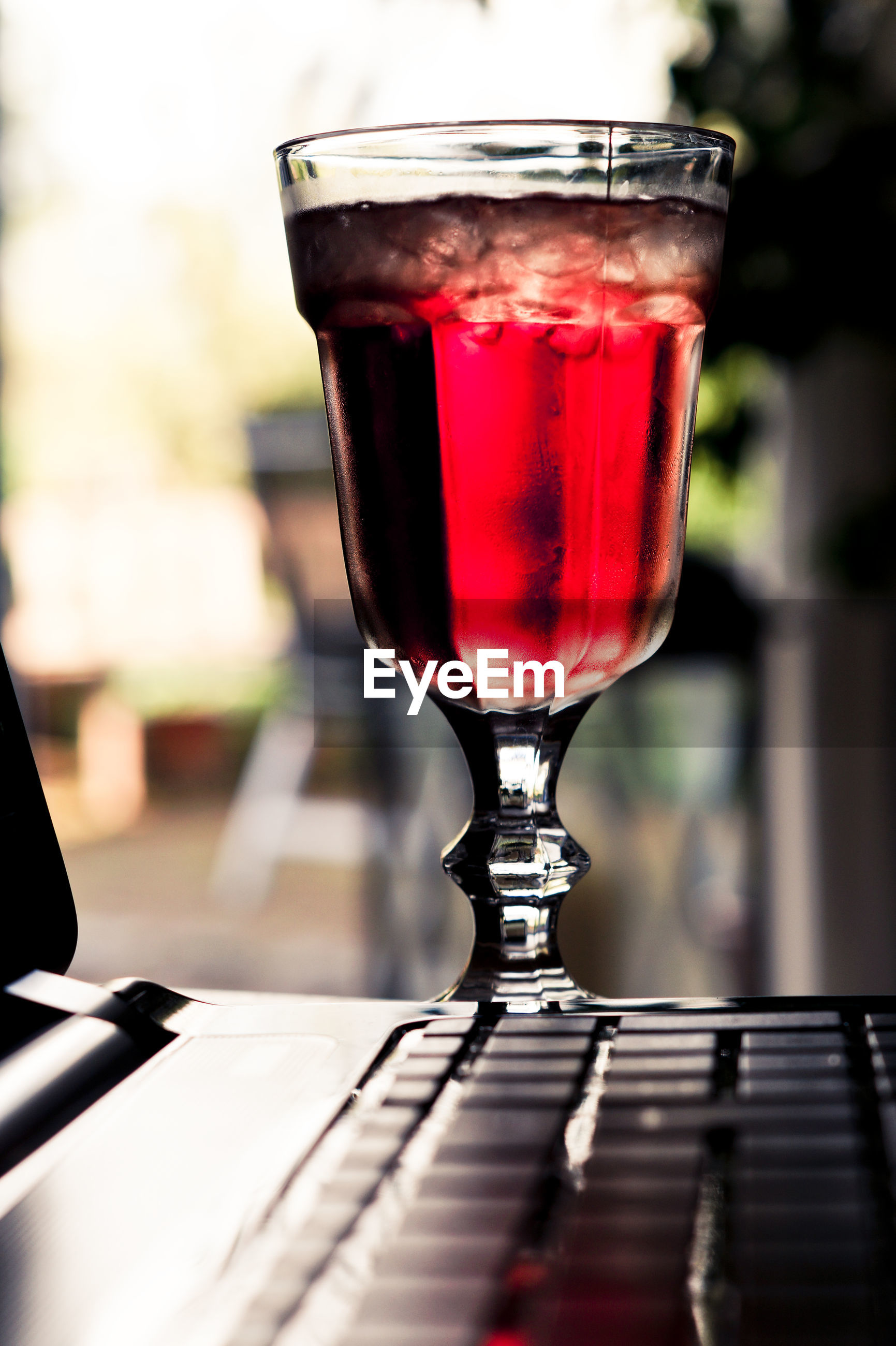 Close-up of red drink in glass by laptop on table