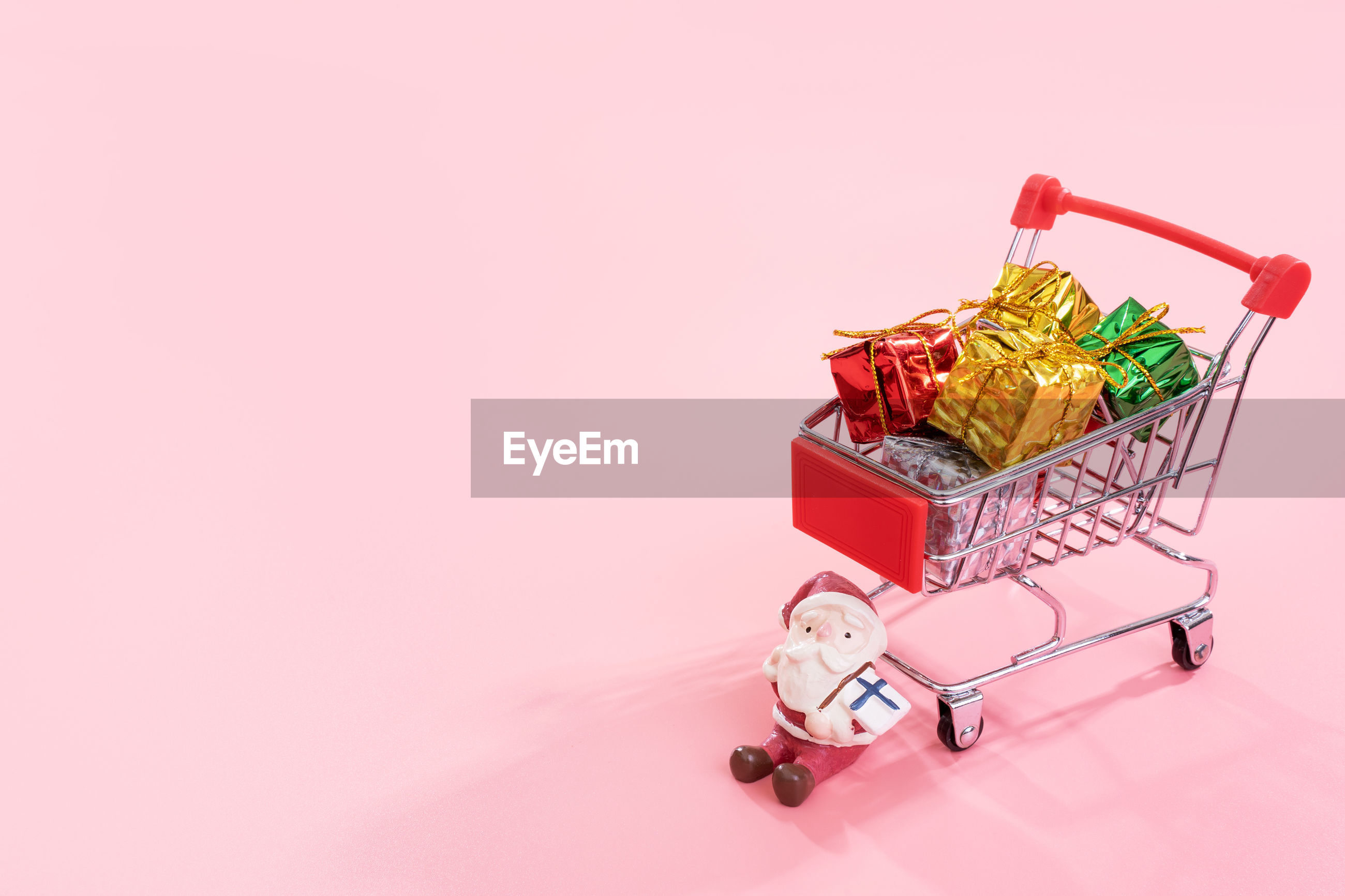Small christmas presents in shopping cart against colored background