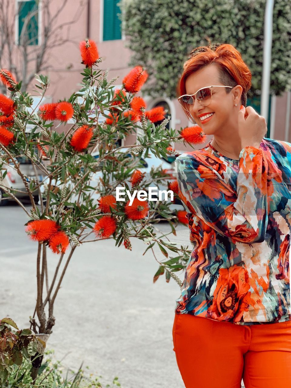 Smiling woman wearing sunglasses standing by plants