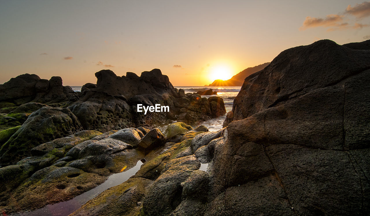 sky, rock, sunset, beauty in nature, scenics - nature, rock - object, solid, nature, tranquil scene, tranquility, non-urban scene, land, no people, rock formation, orange color, idyllic, environment, mountain, sun, cloud - sky, outdoors, eroded