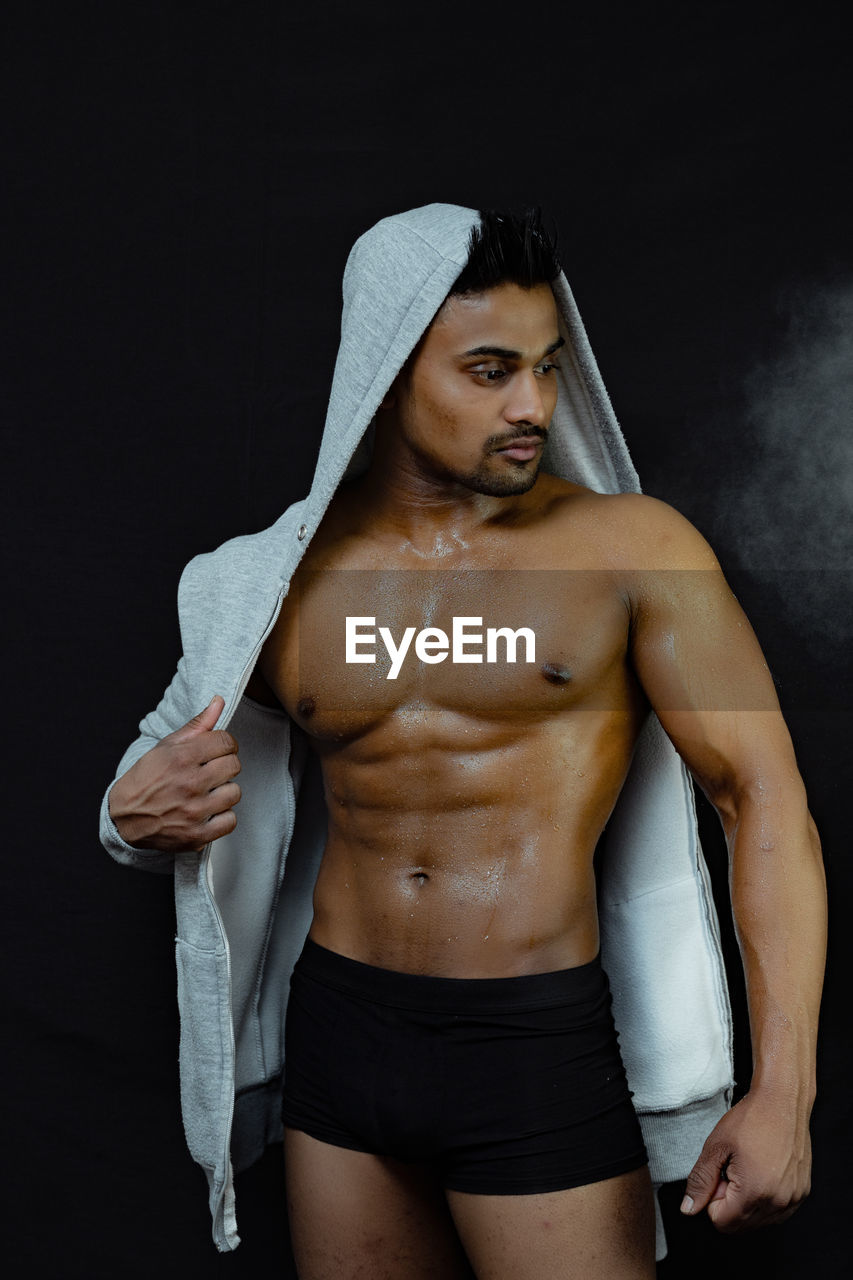 muscular build, shirtless, one person, young adult, strength, lifestyles, indoors, three quarter length, front view, black background, hood, healthy lifestyle, studio shot, young men, adult, standing, looking at camera, men, clothing, hood - clothing, abdominal muscle, masculinity