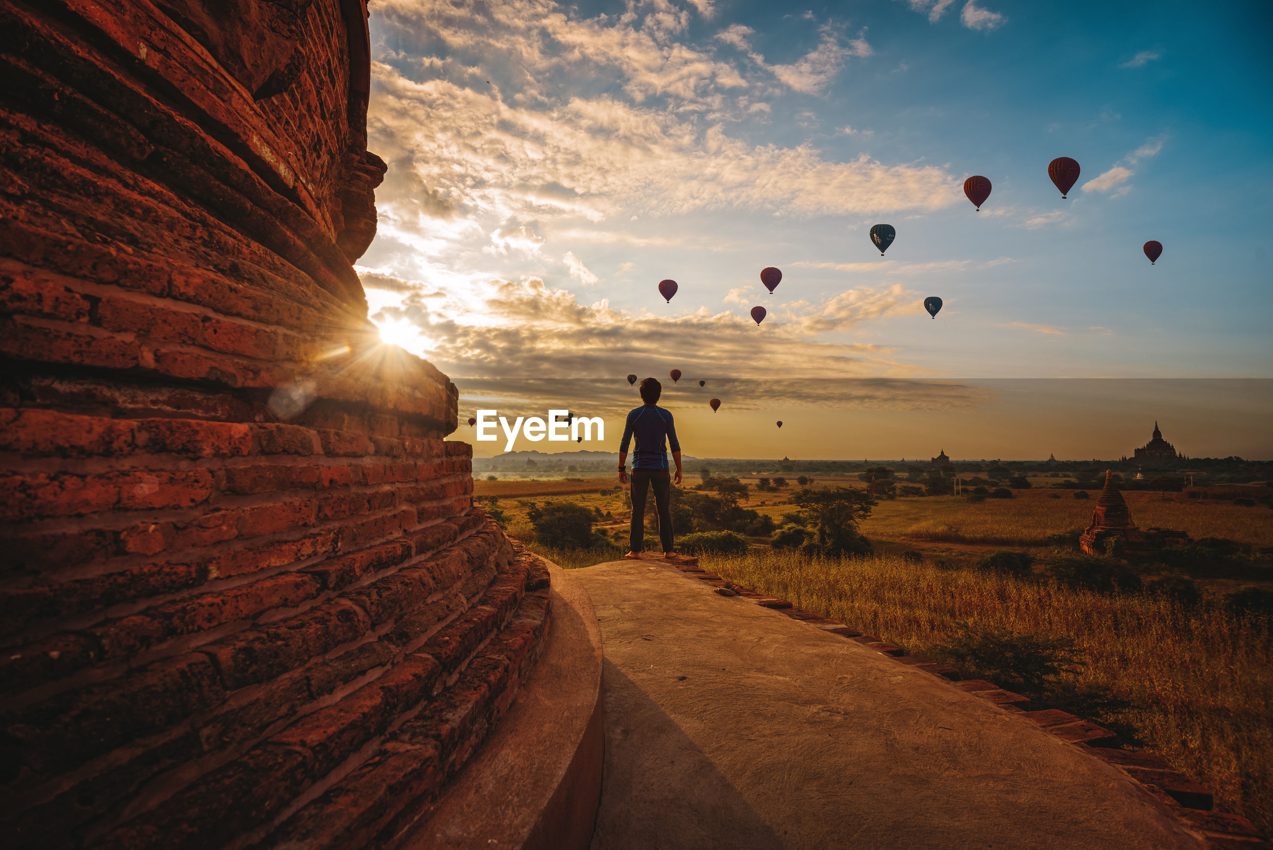 Rear view of man standing against hot air balloons flying in sky during sunset