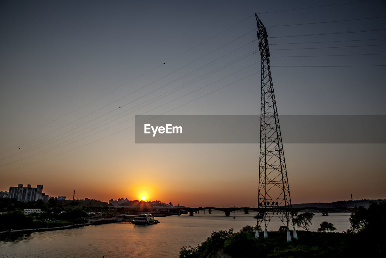 Low angle view of silhouette electricity pylon by han river against sky
