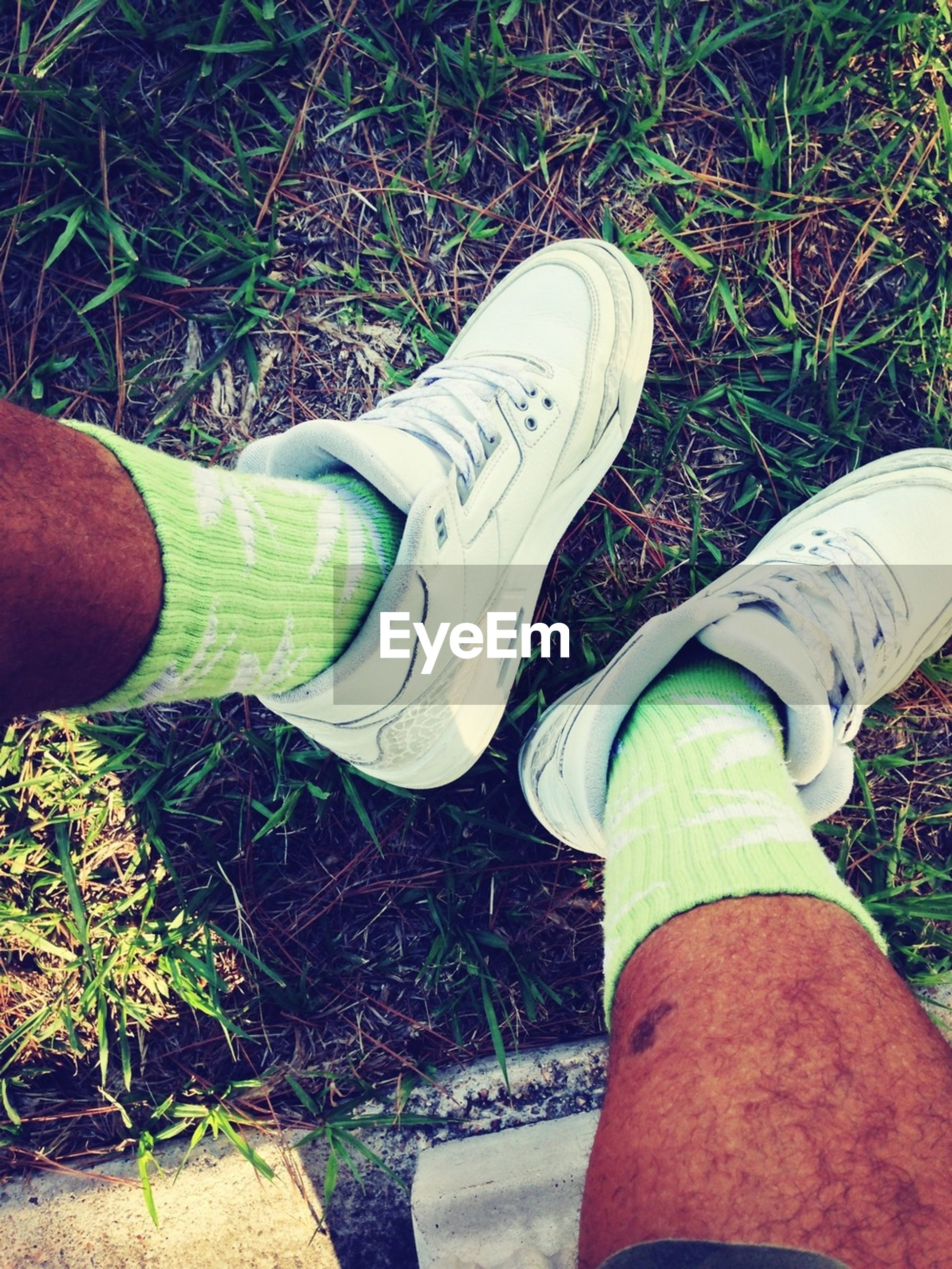 low section, person, shoe, personal perspective, grass, lifestyles, footwear, human foot, part of, leisure activity, jeans, standing, canvas shoe, field, men, legs crossed at ankle, human limb