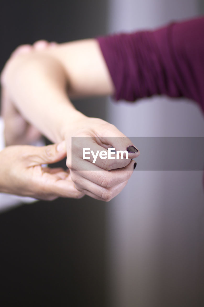 human hand, hand, one person, focus on foreground, real people, human body part, midsection, indoors, lifestyles, women, close-up, adult, body part, front view, leisure activity, jewelry, selective focus, casual clothing, human finger, finger