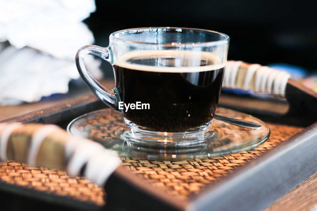 Close-Up Of Cup Of Black Coffee Served In Glass Cup On Tray
