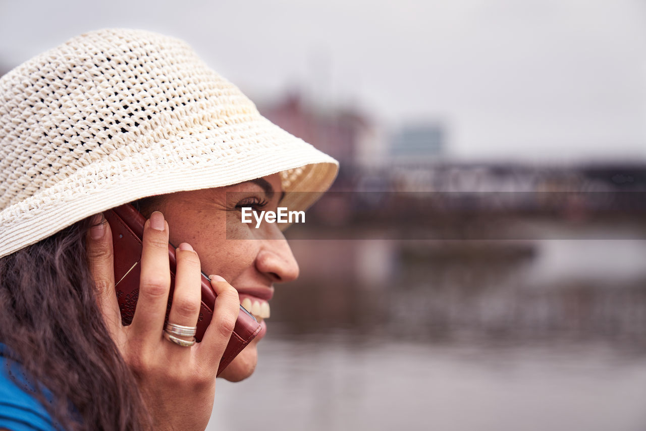Close-Up Of Smiling Woman Talking On Phone By River