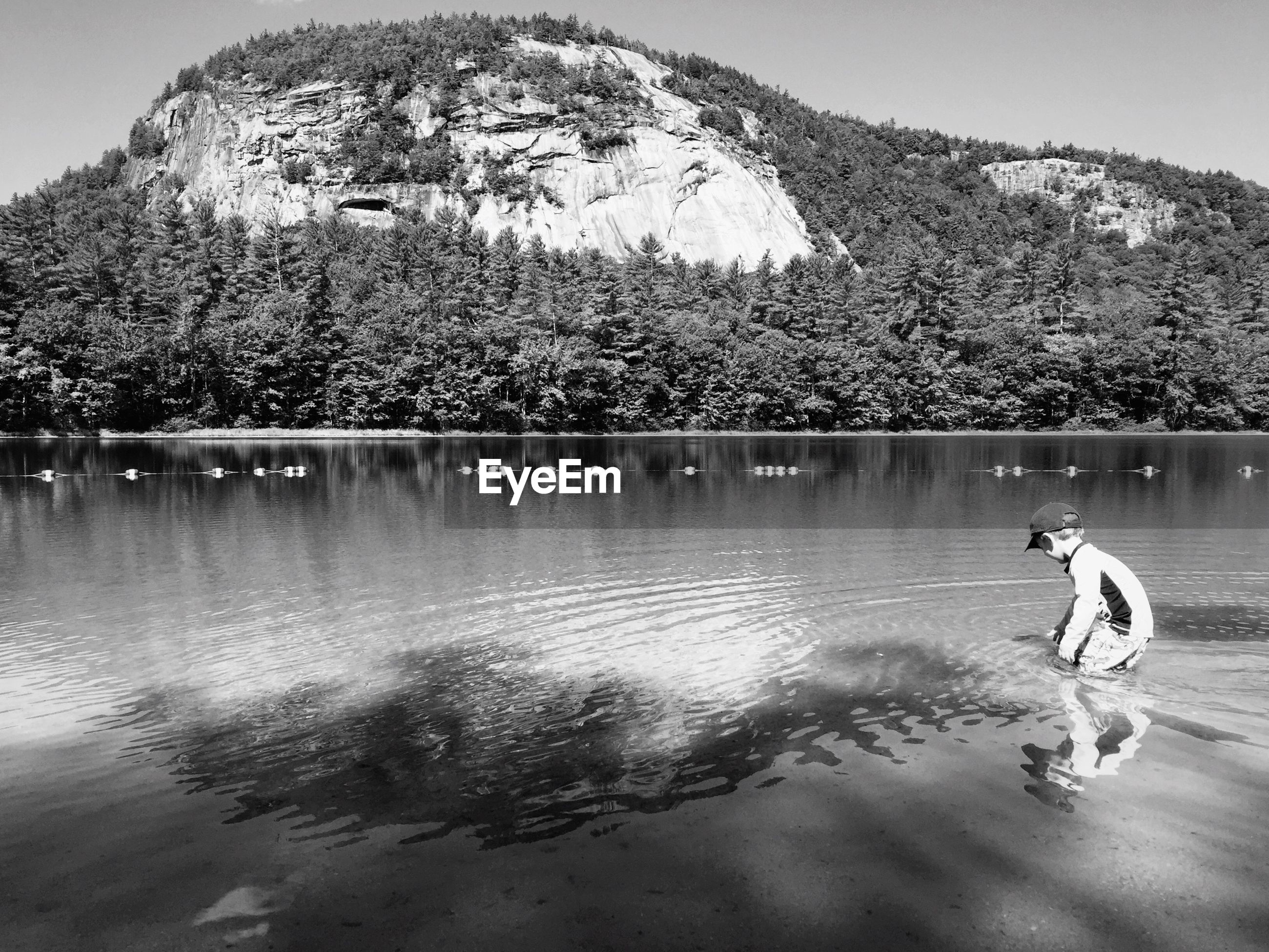 Side view of boy playing in lake against mountain