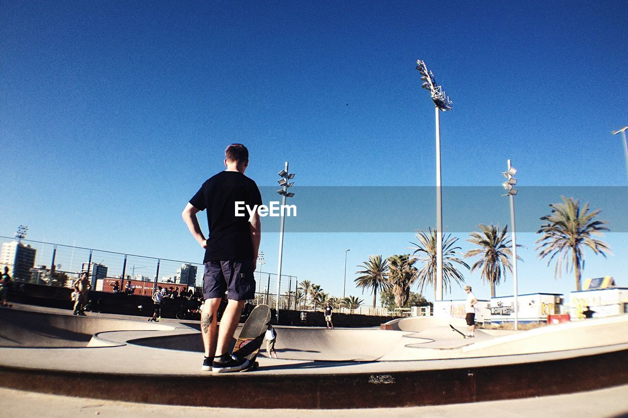 Rear View Of Skateboarder Standing At Skateboard Park Against Clear Sky