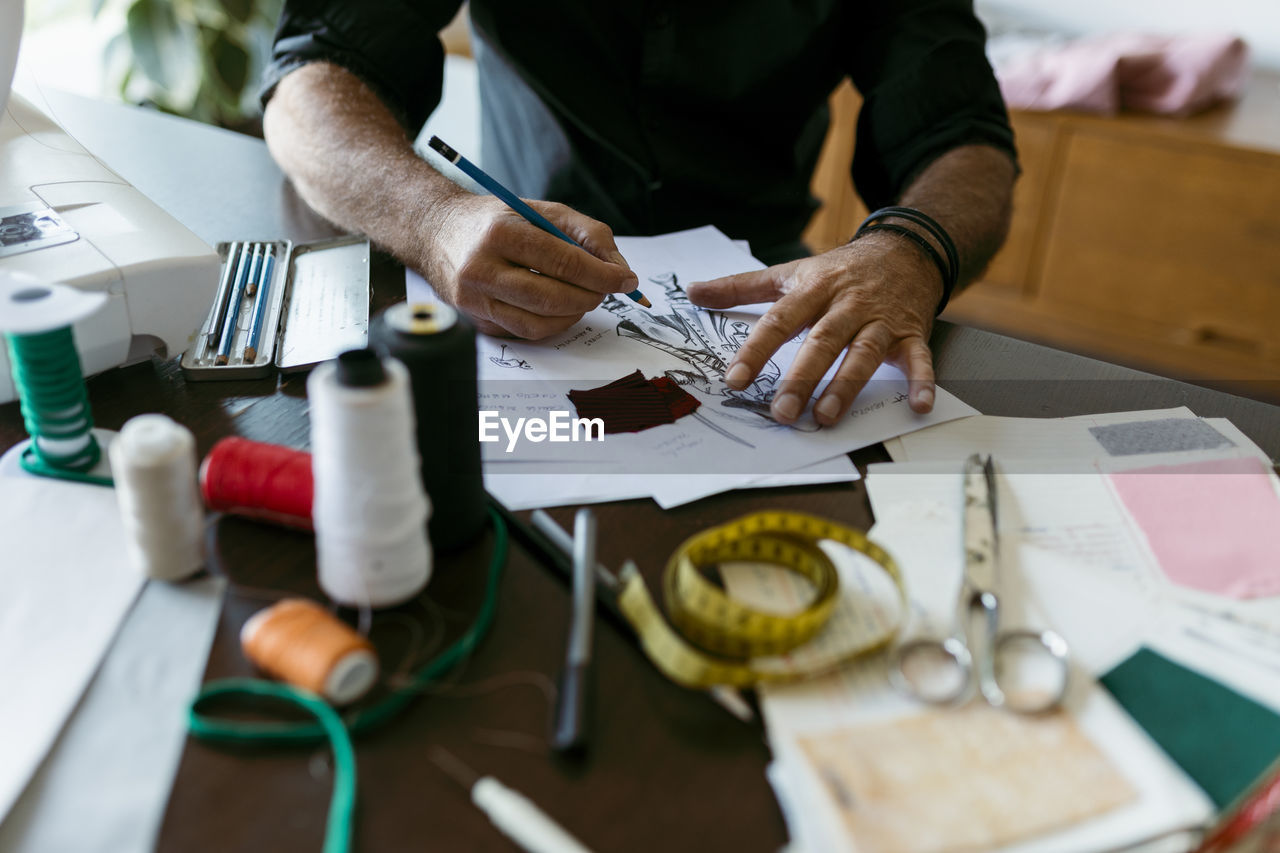 MIDSECTION OF MAN WORKING AT TABLE