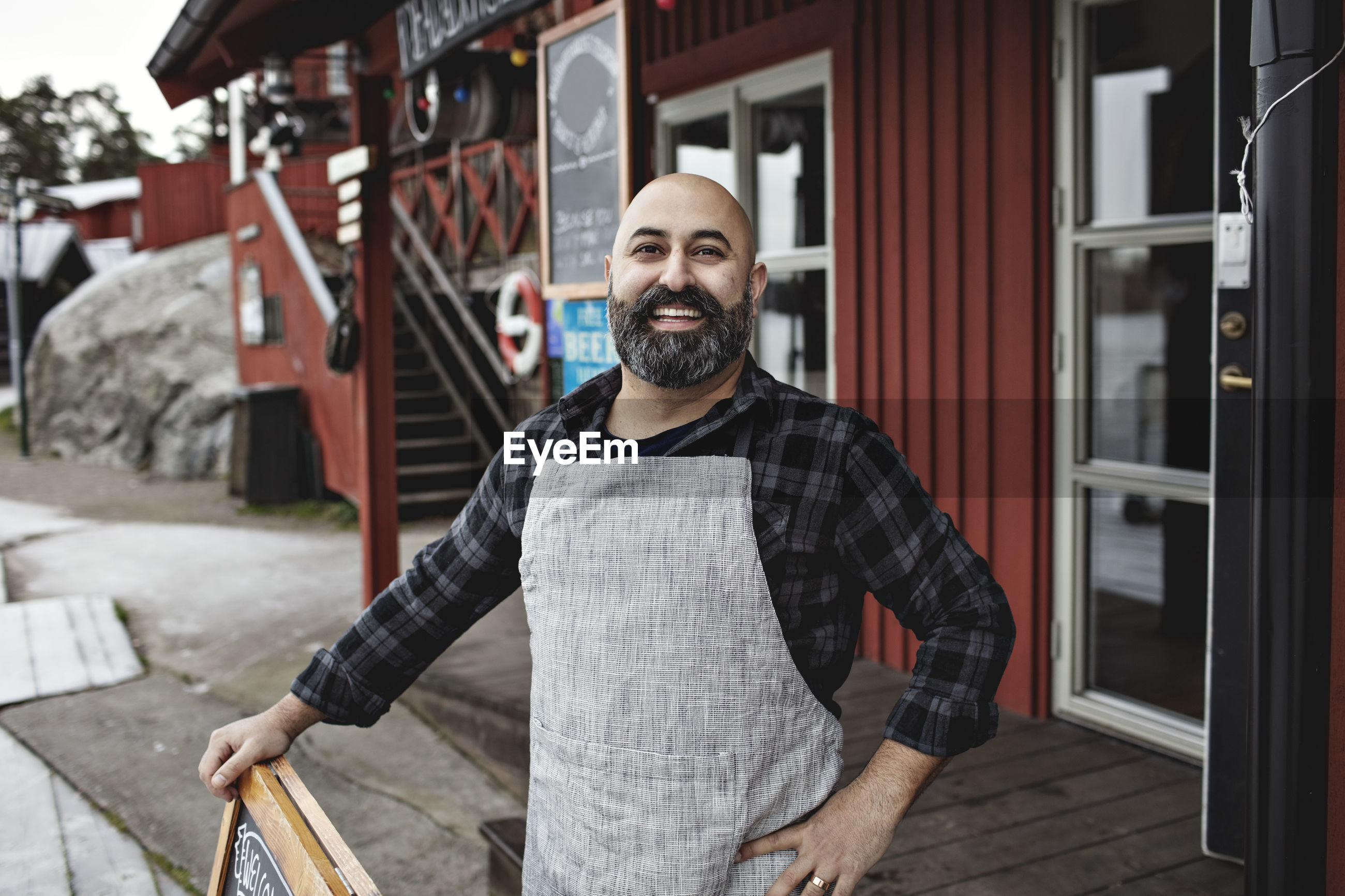 Portrait of smiling worker standing against factory