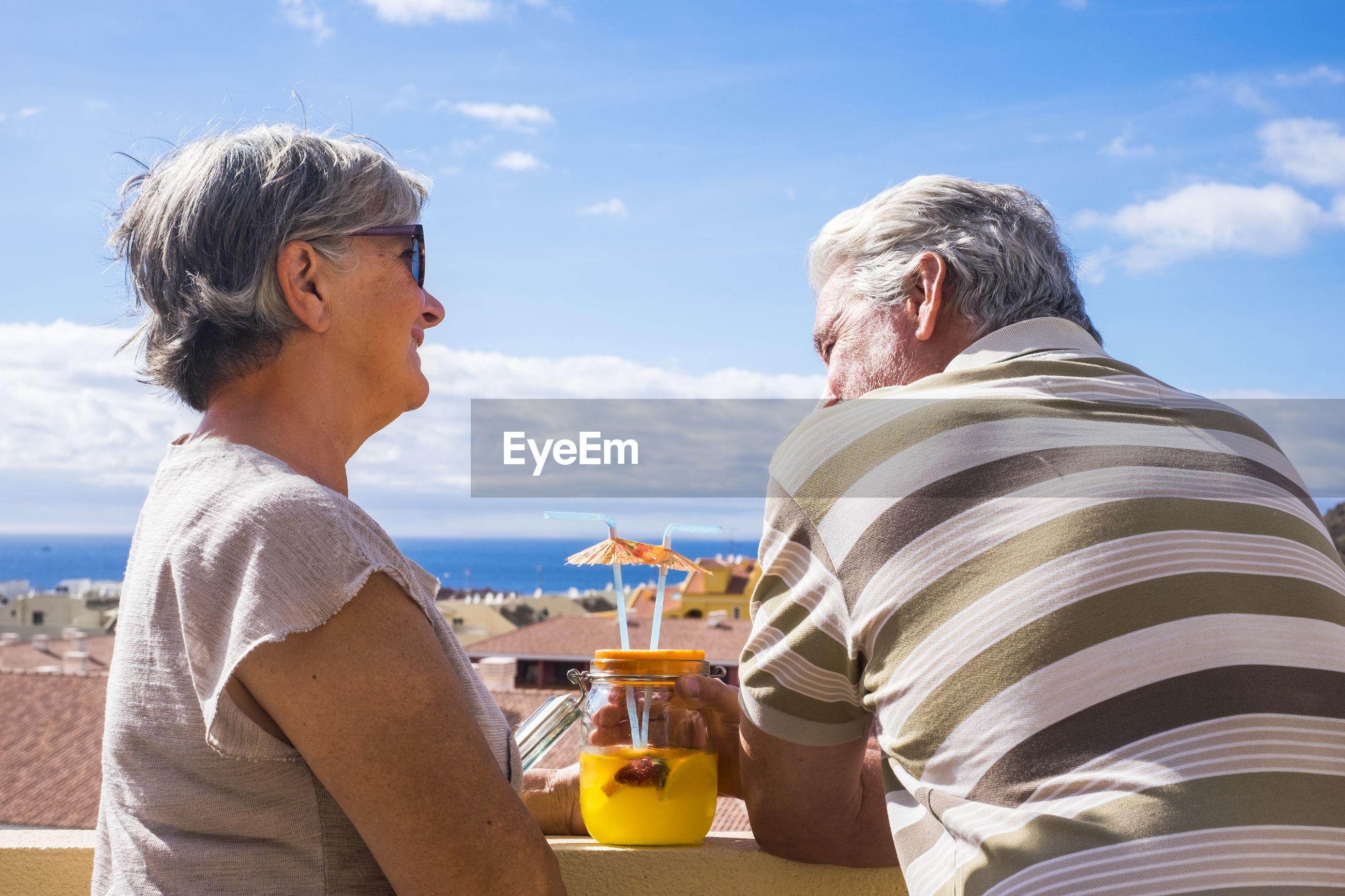Senior couple having drinks in balcony against sky