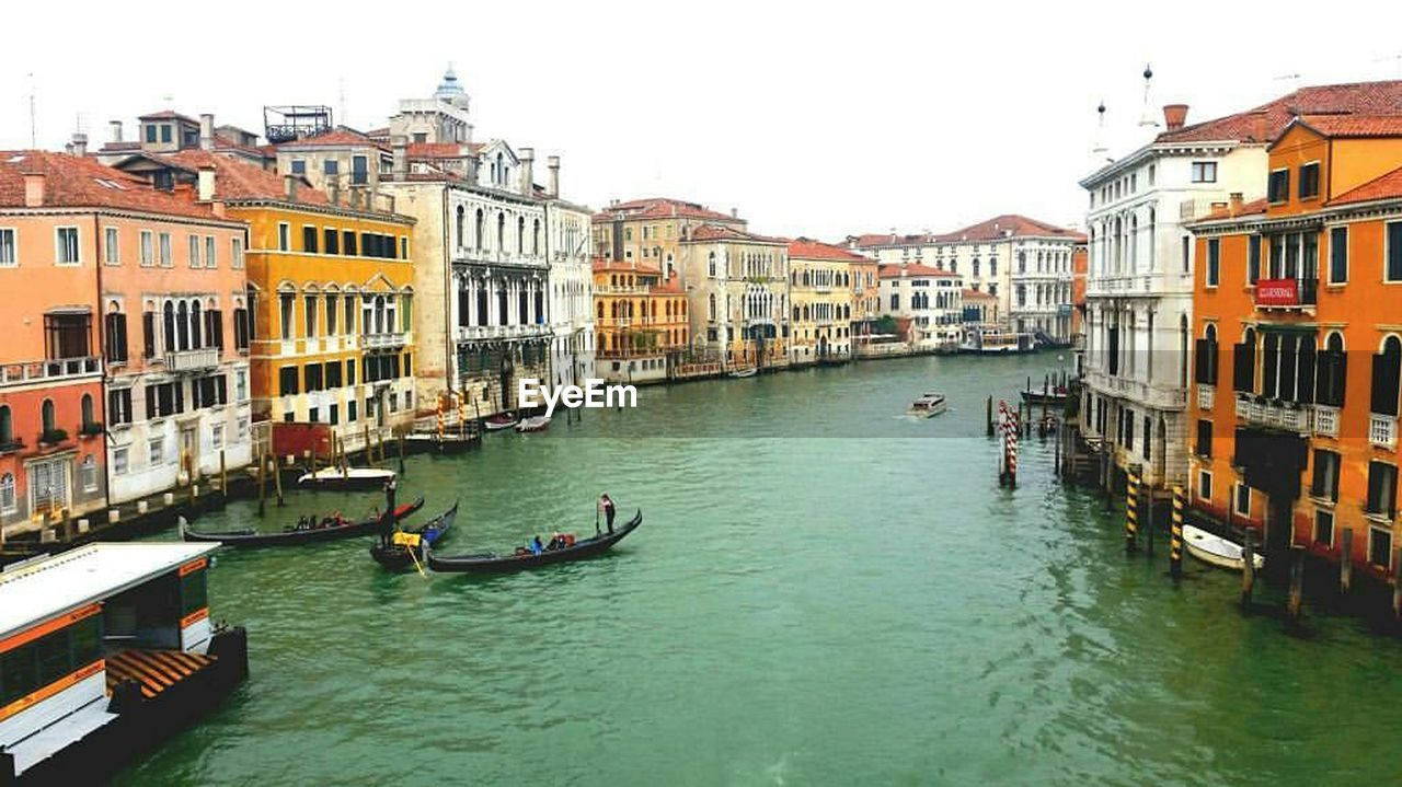 architecture, building exterior, built structure, canal, transportation, nautical vessel, mode of transport, gondola, residential building, water, waterfront, day, gondola - traditional boat, travel destinations, wooden post, outdoors, large group of people, real people, city, people