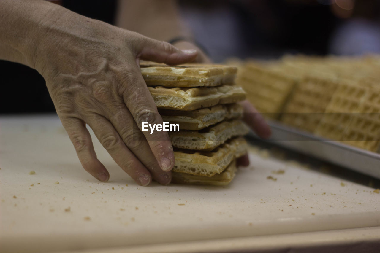 Persons Hand Holding Stack Of Waffles