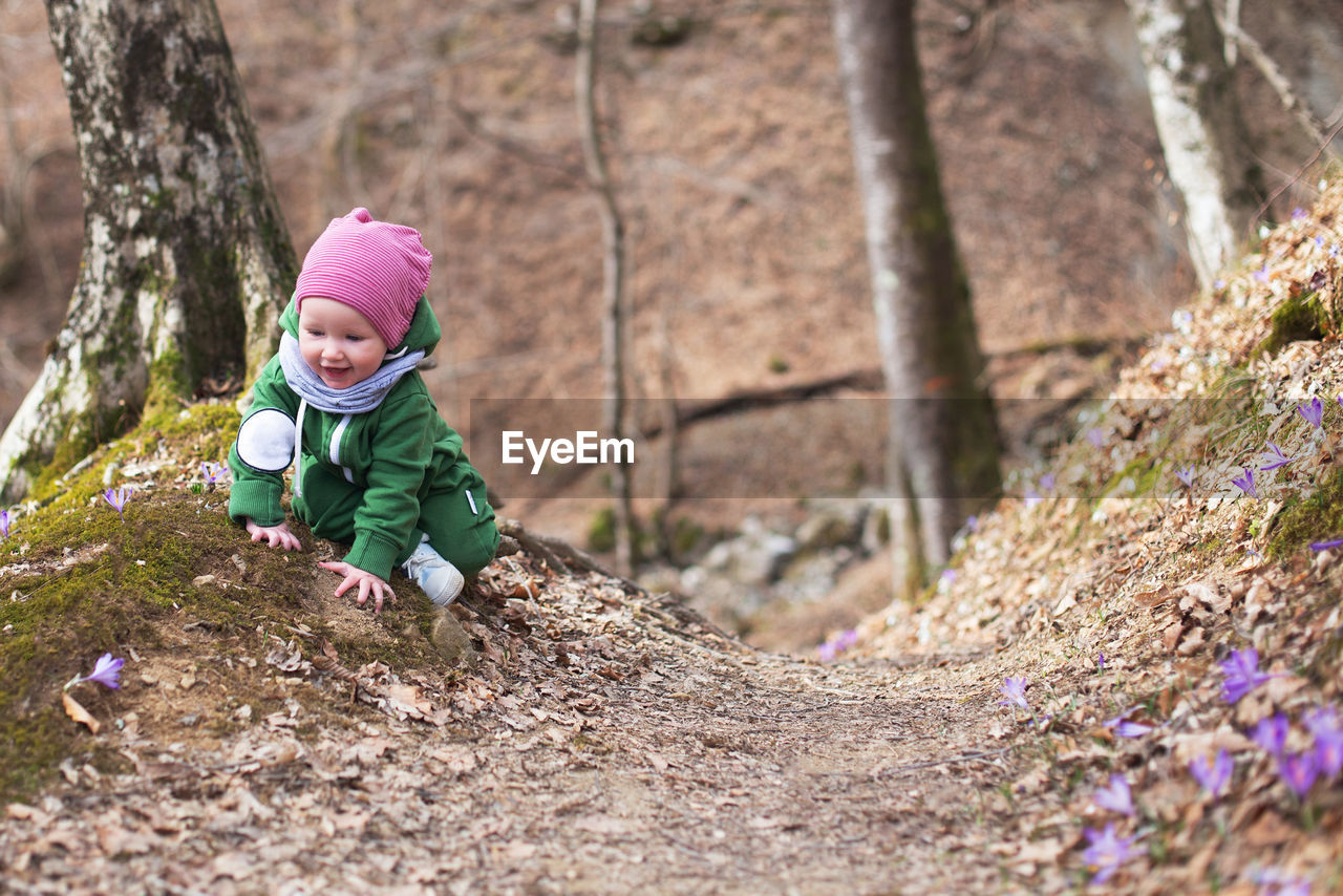 Cute toddler baby on spring forest full of wild irises. spring blossom in the forest. harmony, hope